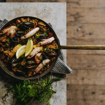 Paella in traditional pan with chorizo and king prawns